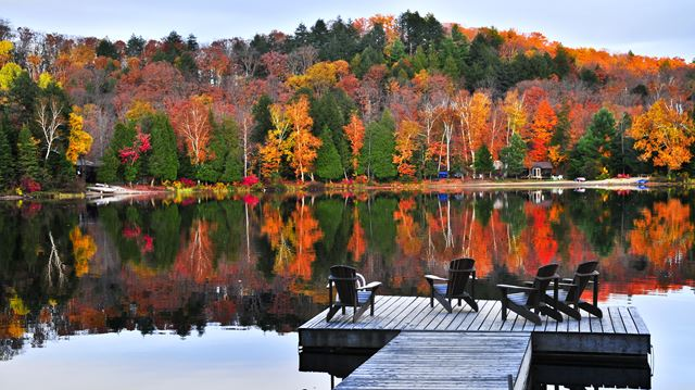 Wooden dock with chairs on calm fall lake